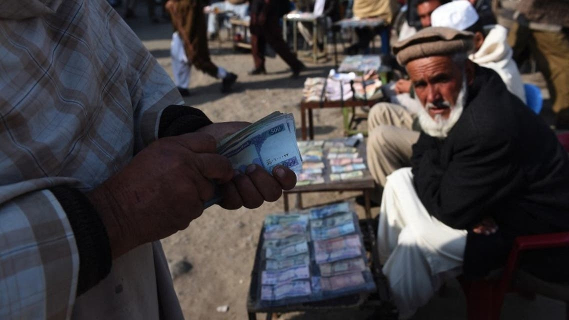 In this photograph taken on December 29, 2014, an Afghan customer (L) counts his Afghani currency notes at a currency exchange market along the roadside in Kabul. (File photo: AFP)