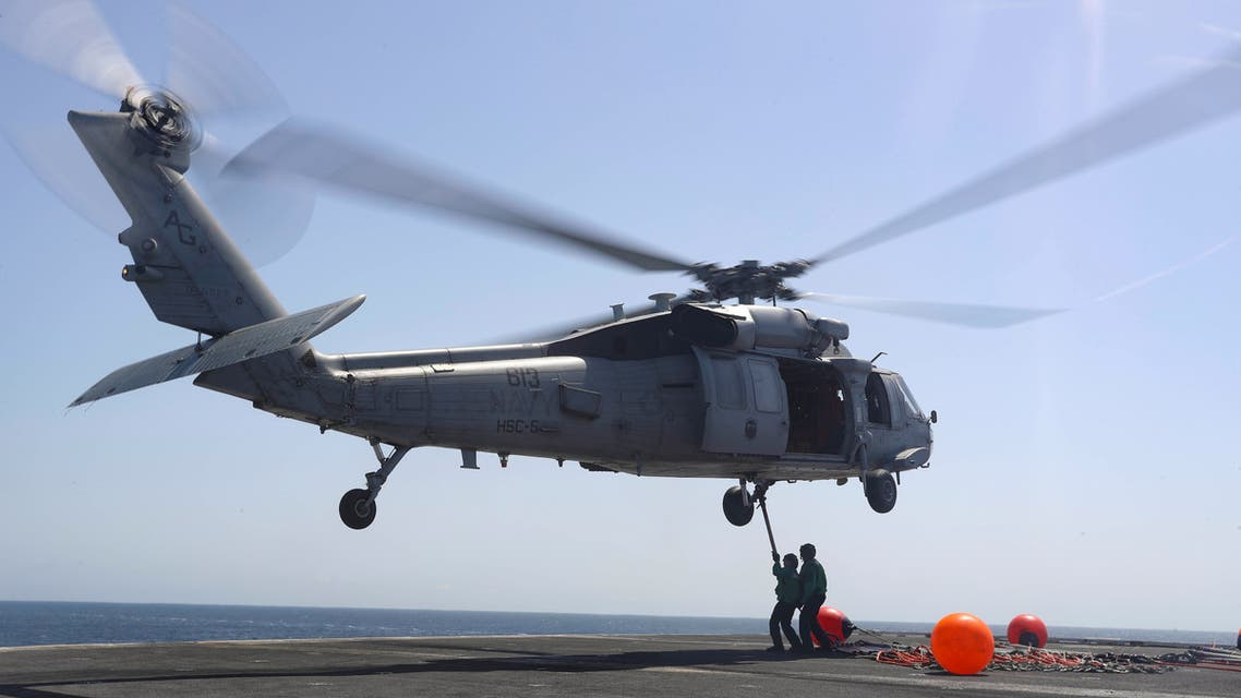 """US Navy sailors connect pogo sticks, used to transport cargo, to an MH-60S Sea Hawk helicopter from the """"Nightdippers"""" of Helicopter Sea Combat Squadron (HSC) 5 on the flight deck of the Nimitz-class aircraft carrier USS Abraham Lincoln (CVN 72) during a replenishment-at-sea, in Arabian Sea, June 7, 2019. (File photo: Reuters)"""