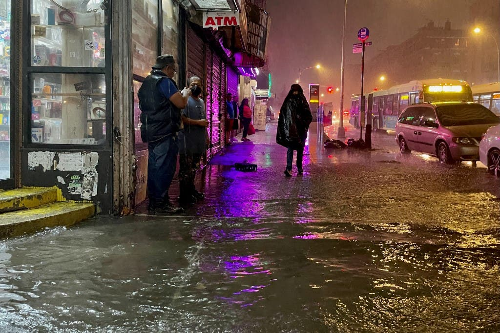 People make their way in rainfall from the remnants of Hurricane Ida on September 1, 2021, in the Bronx borough of New York City. The once category 4 hurricane passed through New York City, dumping 3.15 inches of rain in the span of an hour at Central Park. (AFP)