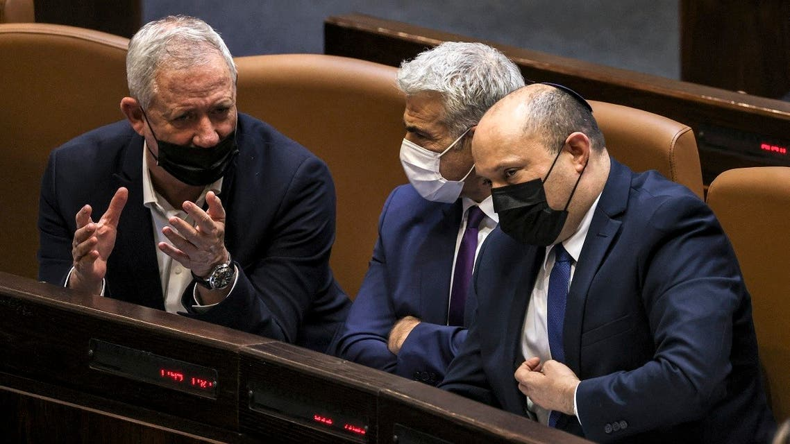 (L to R) Israeli Defense Minister Benny Gantz, Foreign Minister Yair Lapid, and Prime Minister Naftali Bennett sit together to attend a plenum session on the state budget on September 2, 2021. (Ahmad Gharabli/AFP)