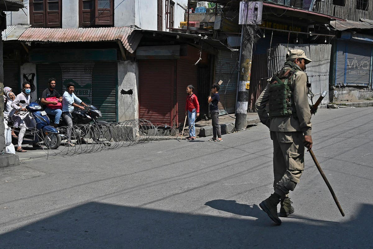 A paramilitary trooper patrols a street as commuters watch in the downtown area of Srinagar on September 3, 2021, as thousands of Indian security forces maintained a lockdown across Kashmir after the death of a separatist political leader sparked clashes with protesters. (AFP)