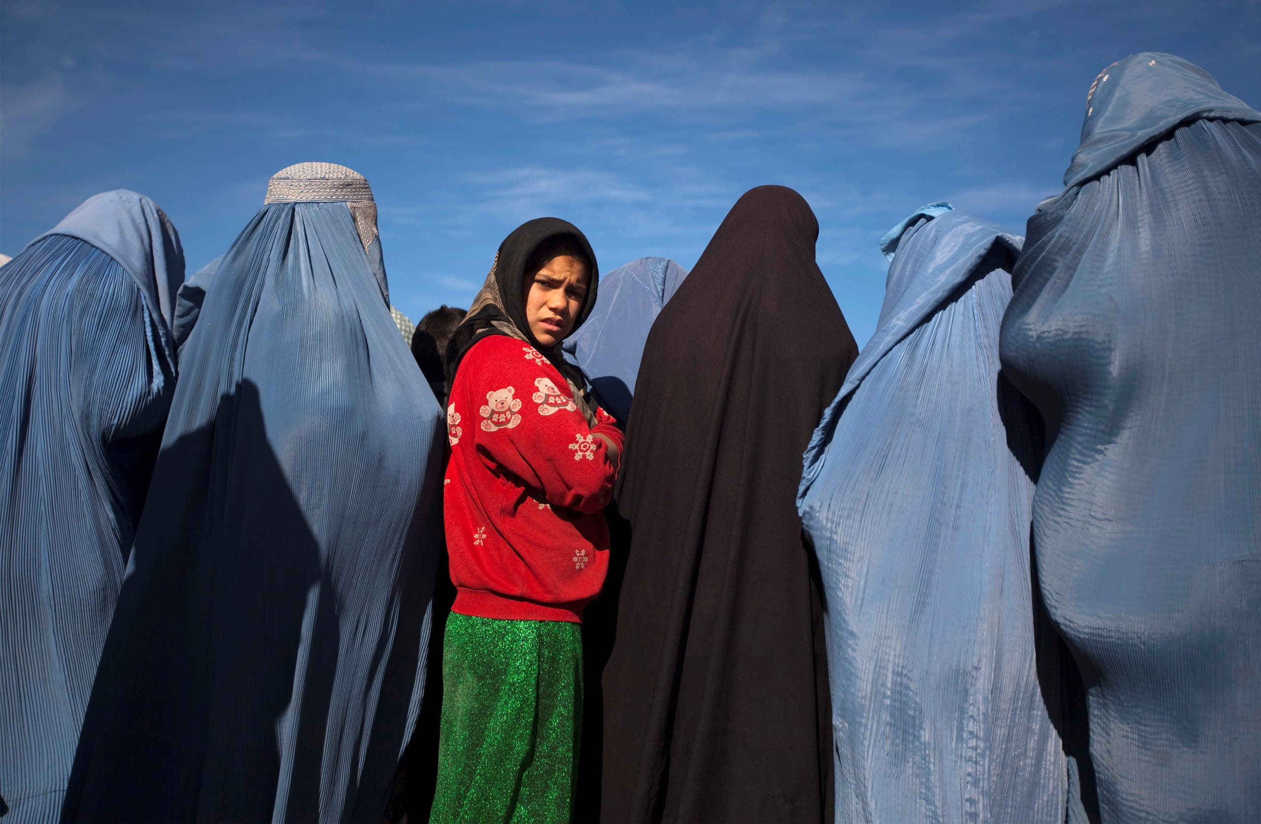 An Afghan girl stands among widows clad in burqas during a cash for work project by humanitarian organisation CARE International in Kabul, Afghanistan January 6, 2010. (Reuters)