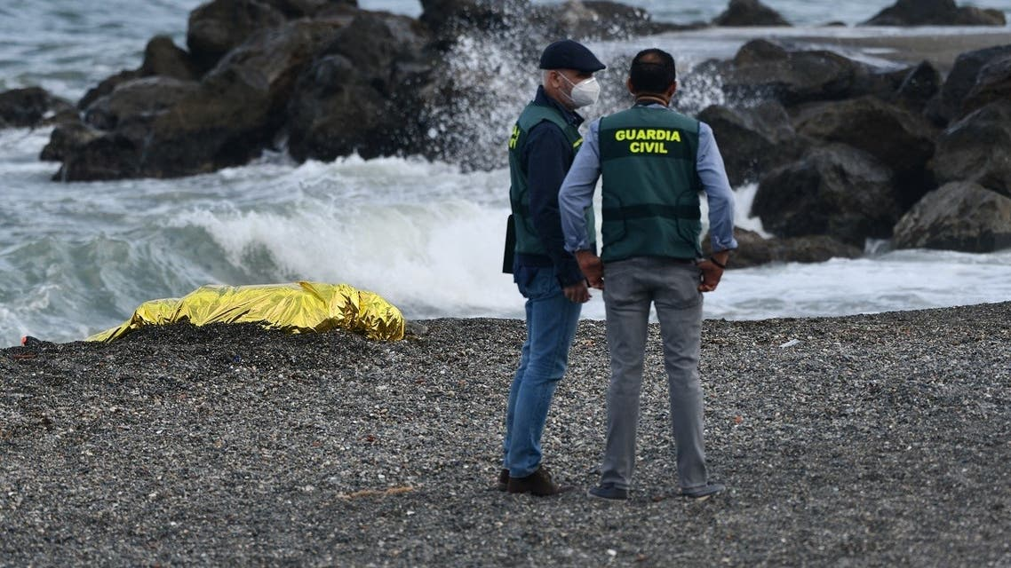 A file photo shows Spanish Guardia Civil members stand next to the body of a migrant at the beach of the Spanish enclave of Ceuta on May 20, 2021. (Antonio Sempere/AFP)