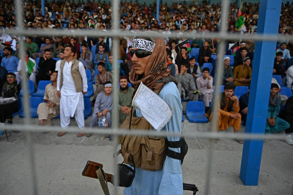 A Taliban fighter (C) keeps vigil as spectators watch the Twenty20 cricket trial match being played between two Afghan teams at the Kabul International Cricket Stadium in Kabul on September 3, 2021. (AFP)