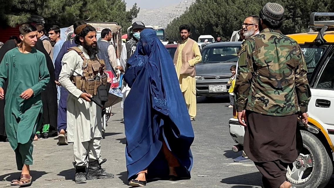 Taliban forces block the roads around the airport, while a woman with Burqa walks passes by, in Kabul, Afghanistan. August 27, 2021. (Reuters)