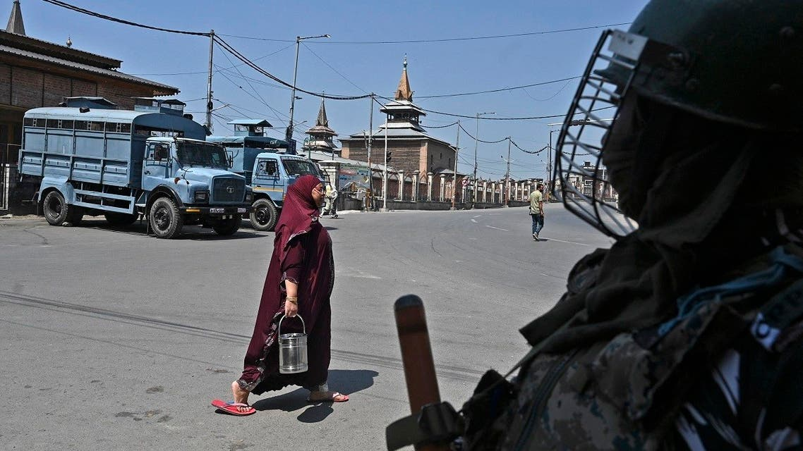 A woman walks past a paramilitary trooper standing on guard near the Jamia Masjid in the downtown area of Srinagar on September 3, 2021, as thousands of Indian security forces maintained a lockdown across Kashmir after the death of a separatist political leader sparked clashes with protesters. (AFP)