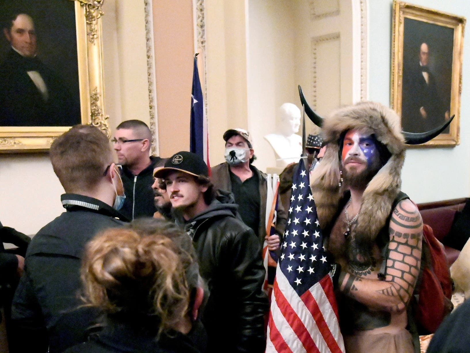 Jacob Anthony Chansley of Arizona stands with other supporters of U.S. President Donald Trump as they demonstrate on the second floor of the U.S. Capitol near the entrance to the Senate after breaching security defenses, in Washington, U.S., January 6, 2021. (File Photo: Reuters)