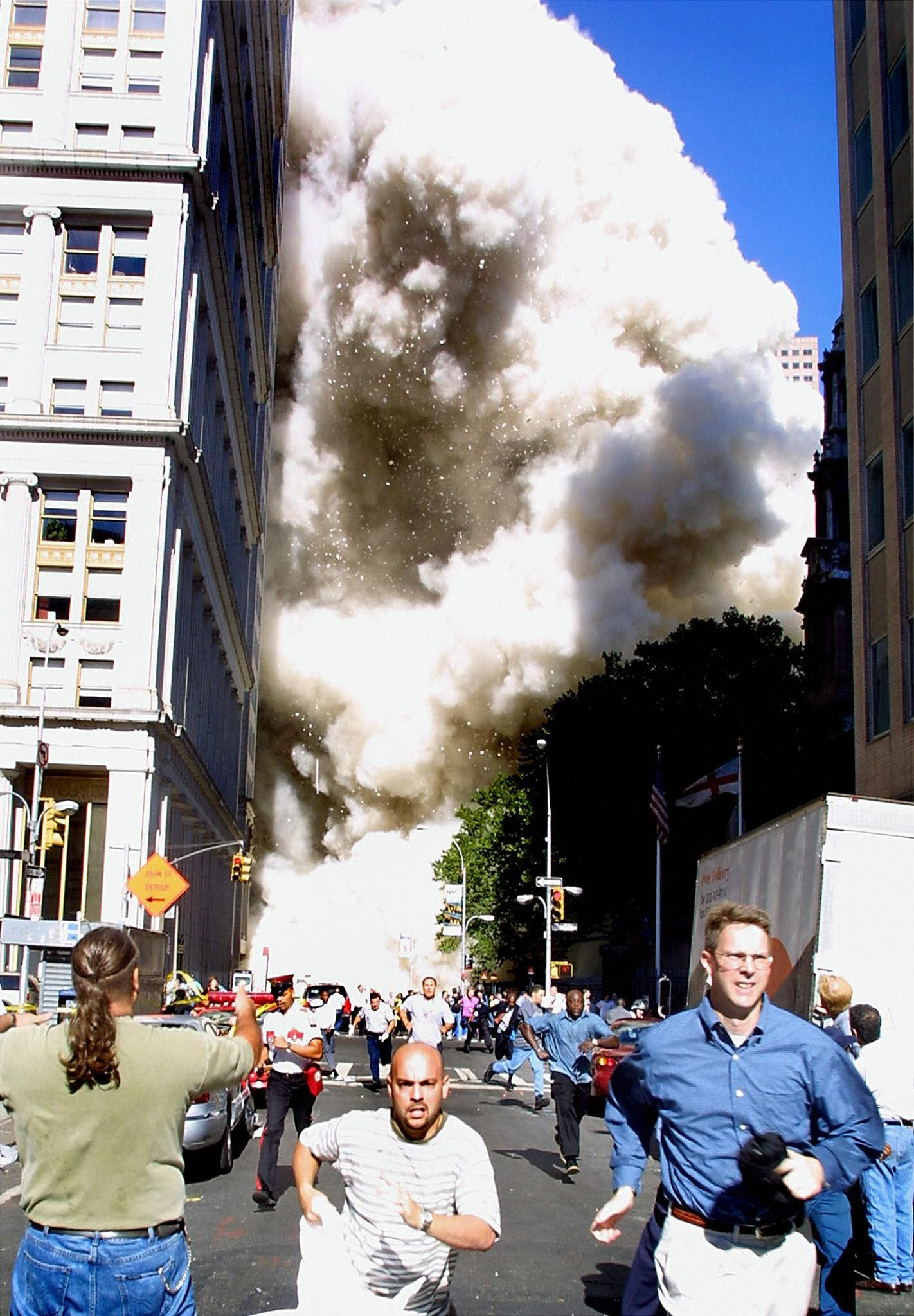This 11 September 2001 file photo shows pedestrians running from the scene as one of the World Trade Center towers collapses in New York City following a terrorist plane crash on the twin towers. (AFP)
