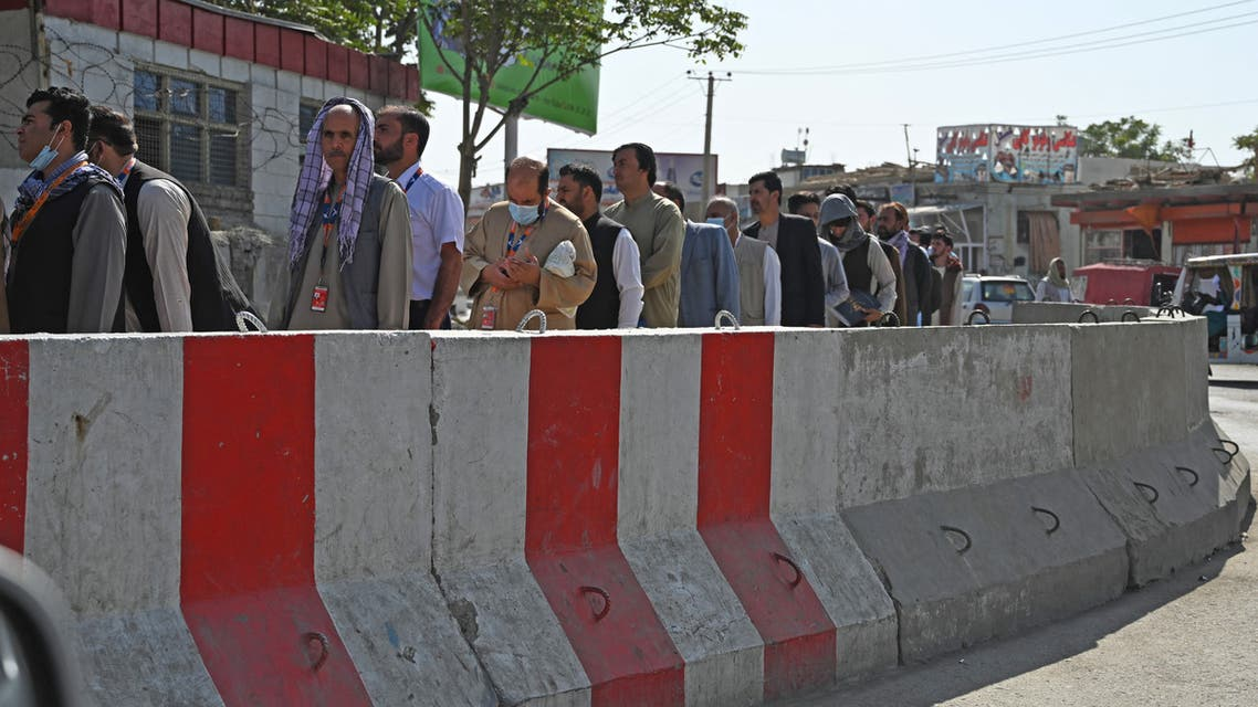 Airport workers stand in a queue at a check point before entering the Kabul International Airport in Kabul on September 4, 2021.