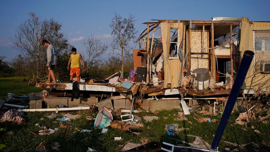 Aiden Locobon, left, and Rogelio Paredes look through the remnants of their family's home destroyed by Hurricane Ida, Saturday, Sept. 4, 2021, in Dulac, La. (AP)