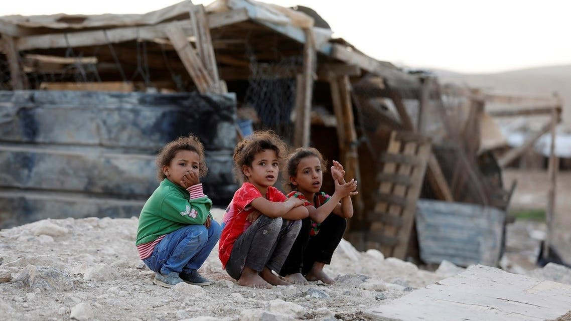 Girls squat in the Palestinian Bedouin village of Khan al-Ahmar, in the occupied West Bank October 22, 2018. (Reuters)