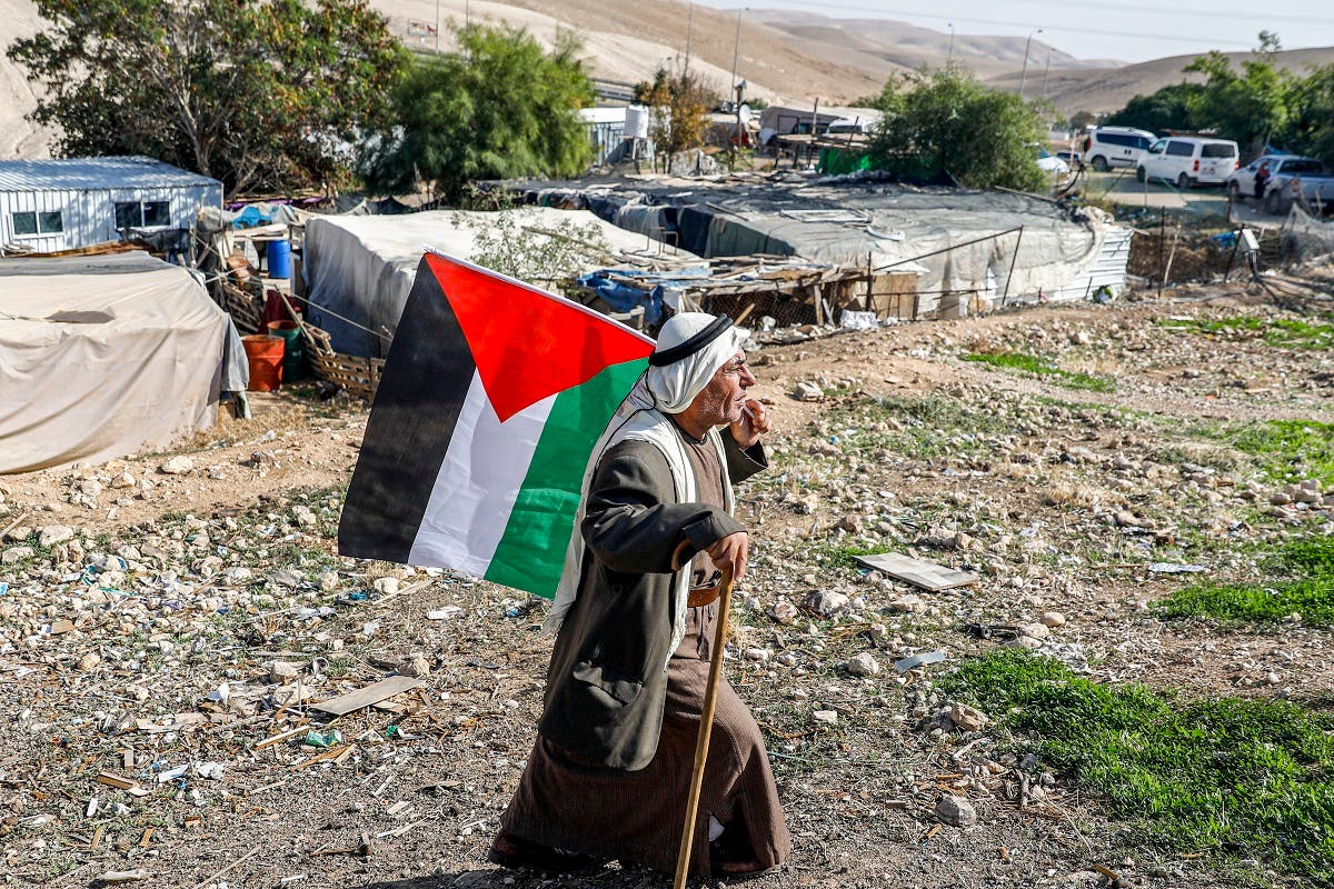 A Bedouin man walks with a Palestinian flag in the village of Khan al-Ahmar in the Israeli-occupied West Bank on November 29, 2020. (AFP)