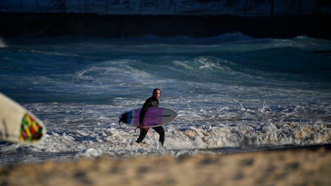 A surfer walks at Bondi Beach in Sydney on August 18, 2021. (AFP)