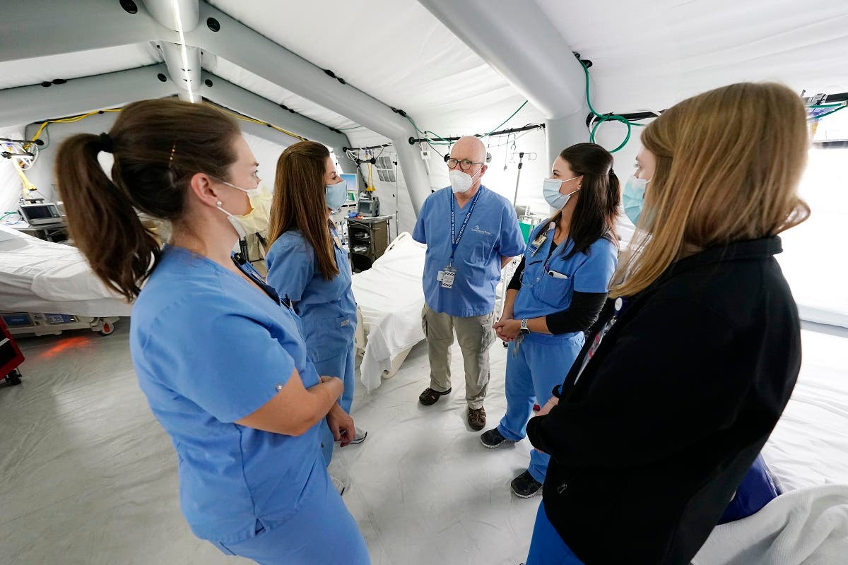 Medical staff confer in one of four wards that are part of the 32-bed Samaritan's Purse Emergency Field Hospital set up in one of the University of Mississippi Medical Center's parking garages, Tuesday, Aug. 17, 2021, in Jackson, Miss. (AP)