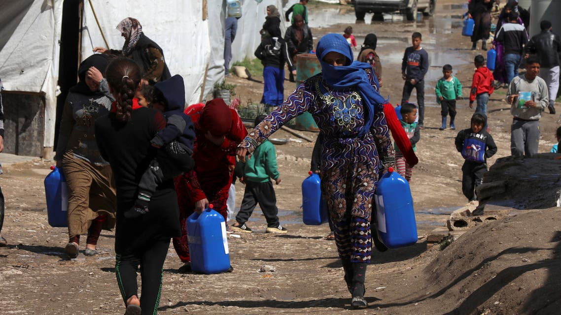 Syrian refugees walk as they carry containers at an informal tented settlement in the Bekaa valley, Lebanon March 12, 2021. (Reuters)