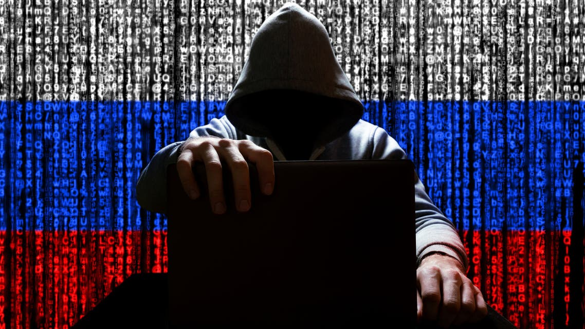 Russian hacker closes the lid of the laptop, against the backdrop of a binary code, the color of the Russian tricolor stock photo