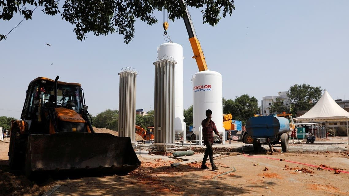 A man walks in front of newly installed oxygen tanks at the construction site of a temporary coronavirus care facility, at Ramlila Ground, in New Delhi, India, May 12, 2021. (Reuters)