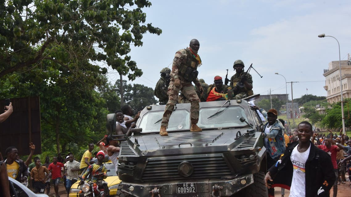 People celebrate in the streets with members of Guinea's armed forces after the arrest of Guinea's president, Alpha Conde, in a coup d'etat in Conakry, September 5, 2021. Guinean special forces seized power in a coup on September 5, arresting the president and imposing an indefinite curfew in the poor west African country.