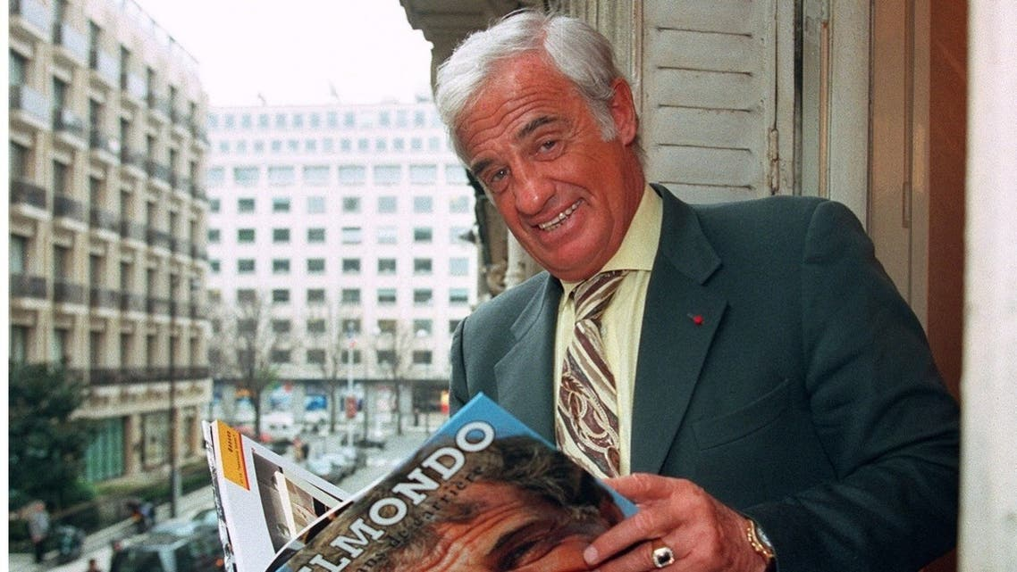 In this file photo taken on April 4, 1996 French actor Jean-Paul Belmondo flips through his biography in Paris. (Vincent Amalvy/AFP)