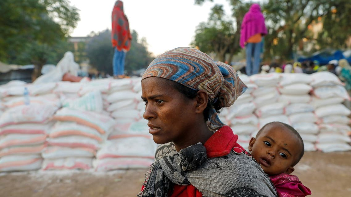 A woman carries an infant as she queues in line for food, at the Tsehaye primary school, which was turned into a temporary shelter for people displaced by conflict, in the town of Shire, Tigray region, Ethiopia, March 15, 2021. Picture taken March 15, 2021. (File Photo: Reuters)