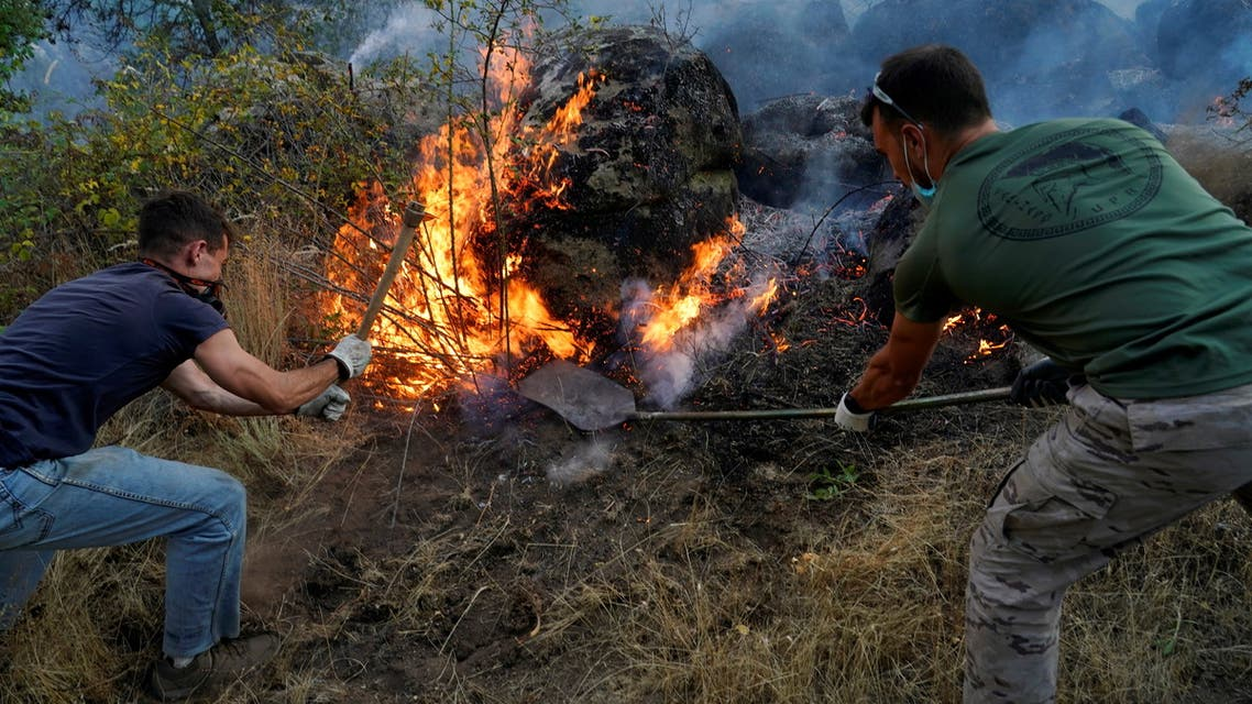 Volunteers try to extinguish a wildfire burning in the village of Navalmoral, Spain, August 16, 2021. (Reuters)
