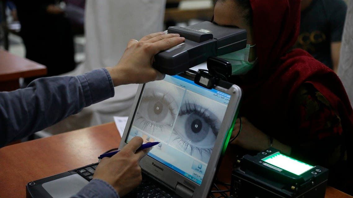 In this June 30, 2021, file photo an employee scans the eyes of a woman for biometric data needed to apply for a passport, at the passport office in Kabul, Afghanistan. (AP)