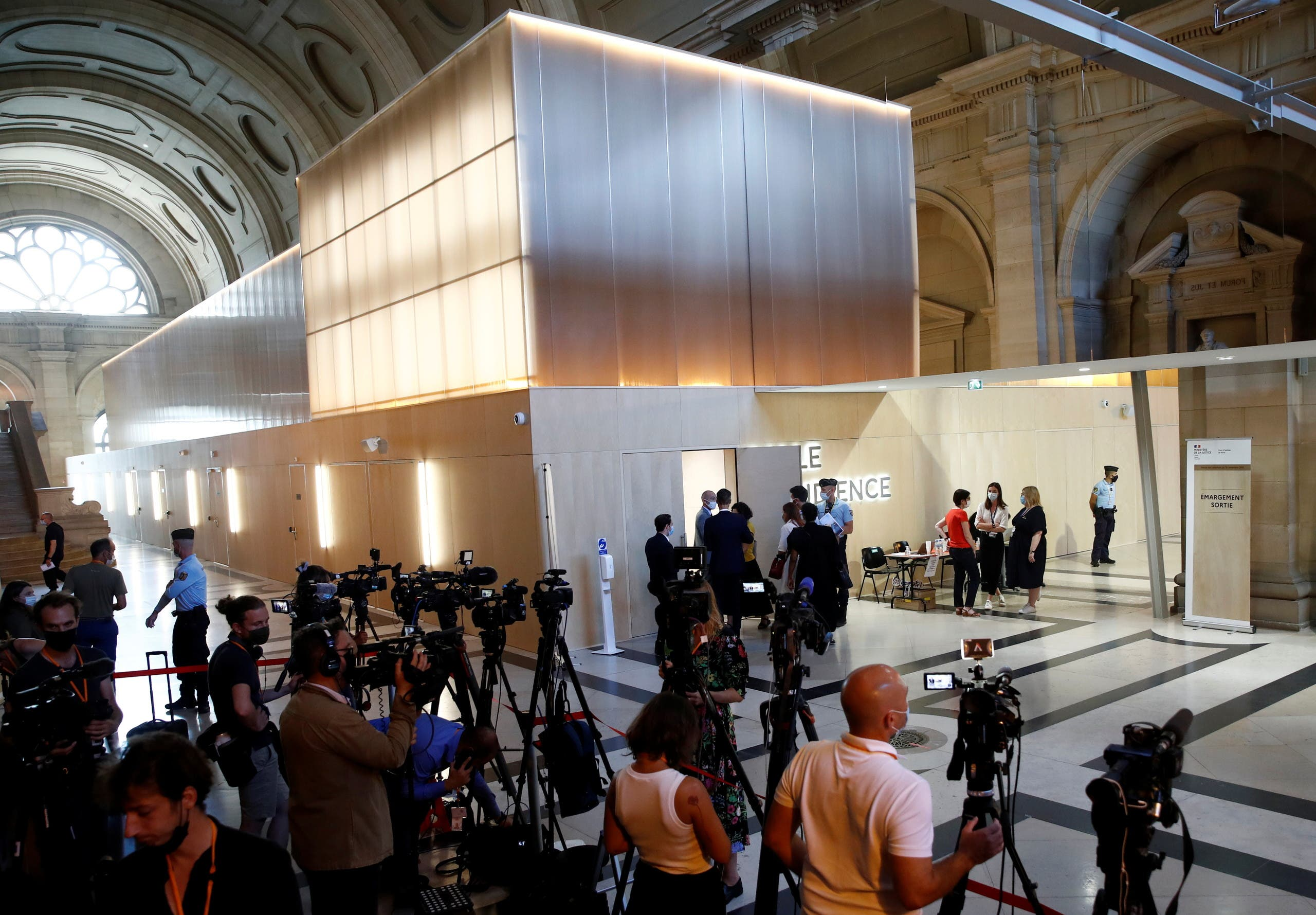 Journalists work in front of the temporary courtroom set up at during the start of the trial of the Paris' November 2015 attacks at the Paris courthouse on the Ile de la Cite, in Paris, France, September 8, 2021. (Reuters)