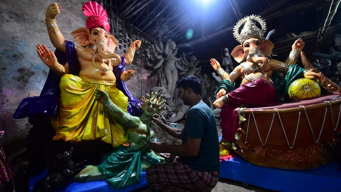 An artist gives the finishing touches to an idol of the elephant-headed Hindu God Ganesha with a figure depicting a coronavirus at a workshop ahead of the Ganesh Chaturthi festival in Allahabad on September 7, 2021. (File photo: AFP)
