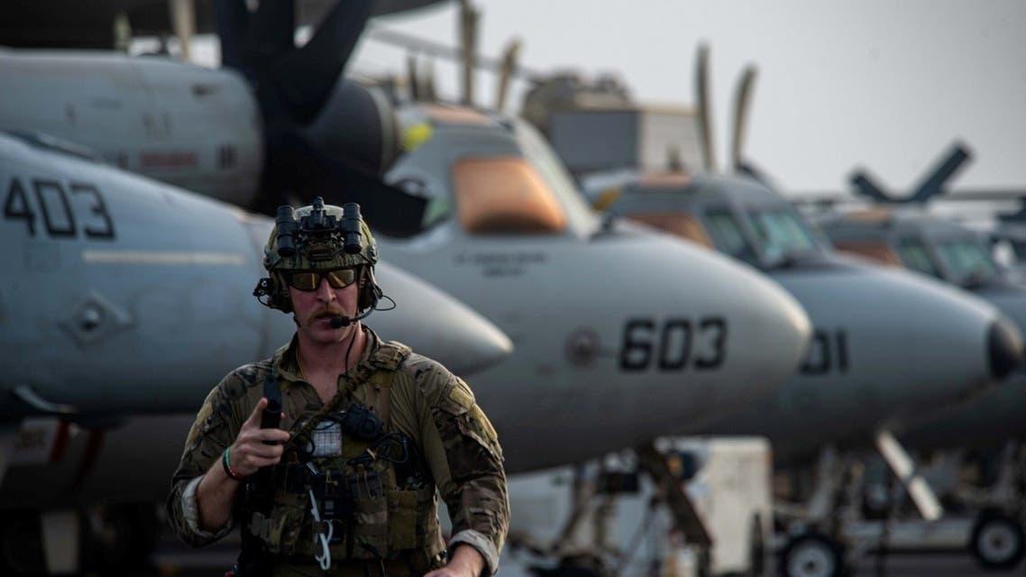 A US Navy service member walks across the flight deck of aircraft carrier USS Ronald Reagan, July 30, 2021. (Reuters)