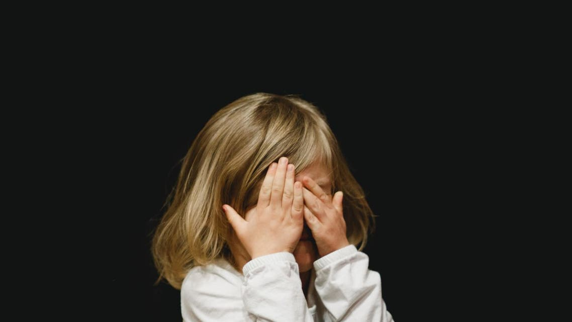 Child covering her face. (Unsplash, Caleb Woods)