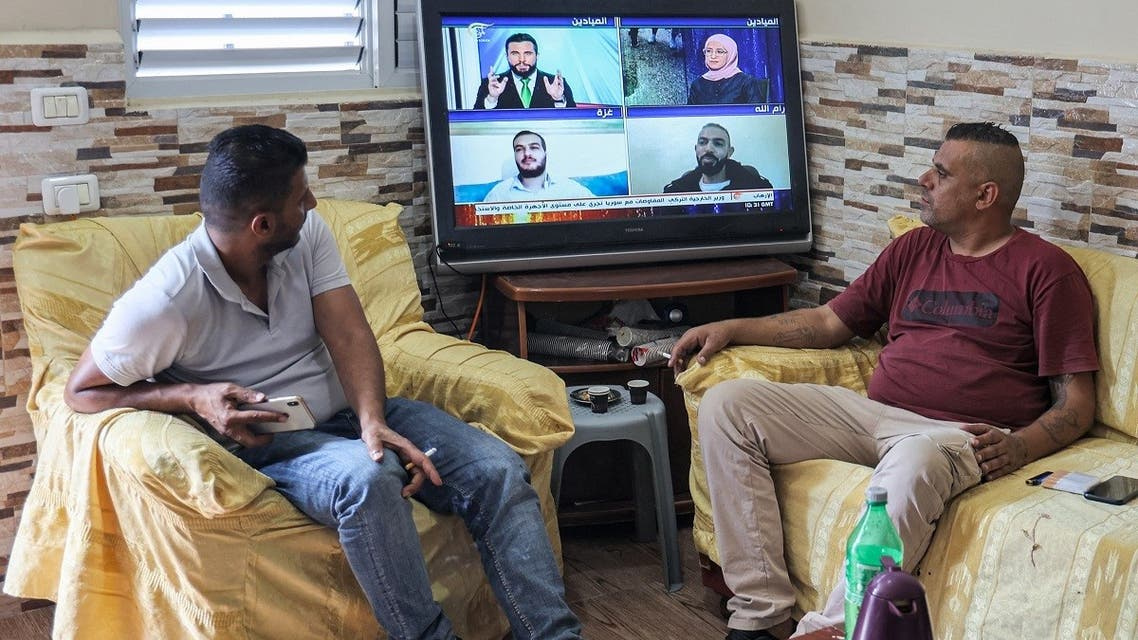 Family members of of Zakaria Zubeidi, one of six Palestinian prisoners who escaped from Israel's Gilboa prison, watch a news bulleting on a television as they await any information about him, at their home in the Jenin camp for Palestinian refugees in the north of the occupied West Bank, on September 7, 2021. (AFP)