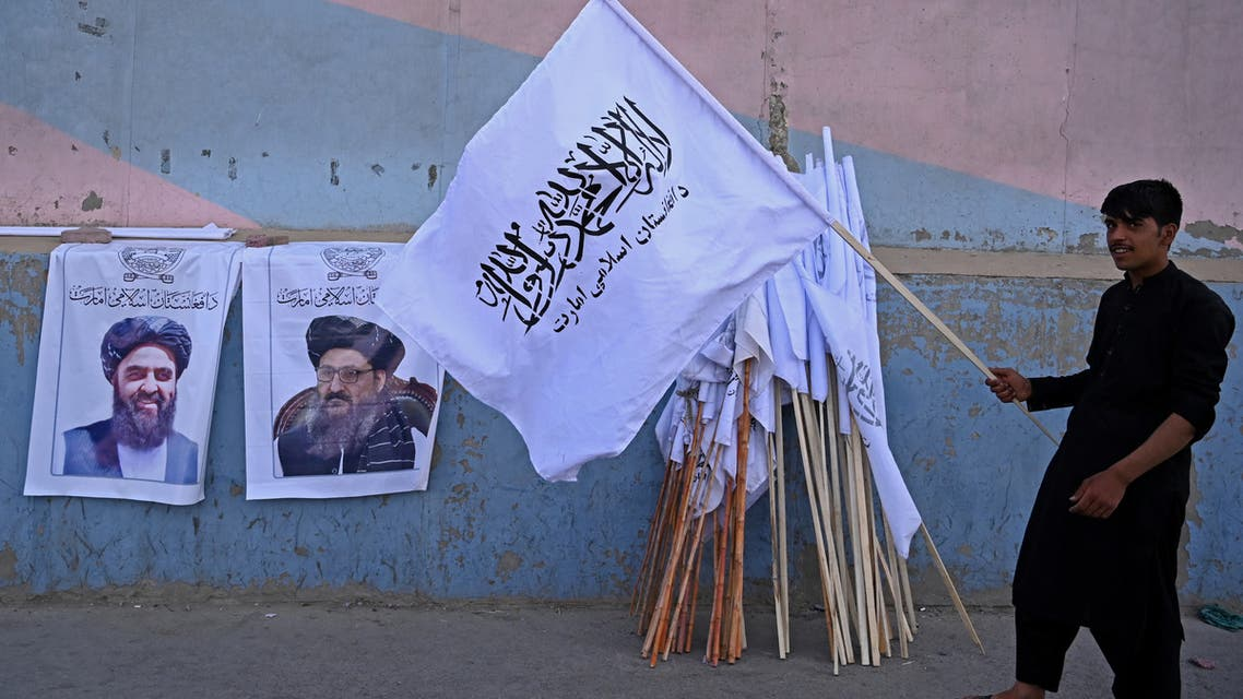 A vendor holds a Taliban flag next to the posters of Taliban leaders Mullah Abdul Ghani Baradar and Amir Khan Muttaqi (L) as he waits for customers along a street in Kabul on August 27, 2021. (AFP)