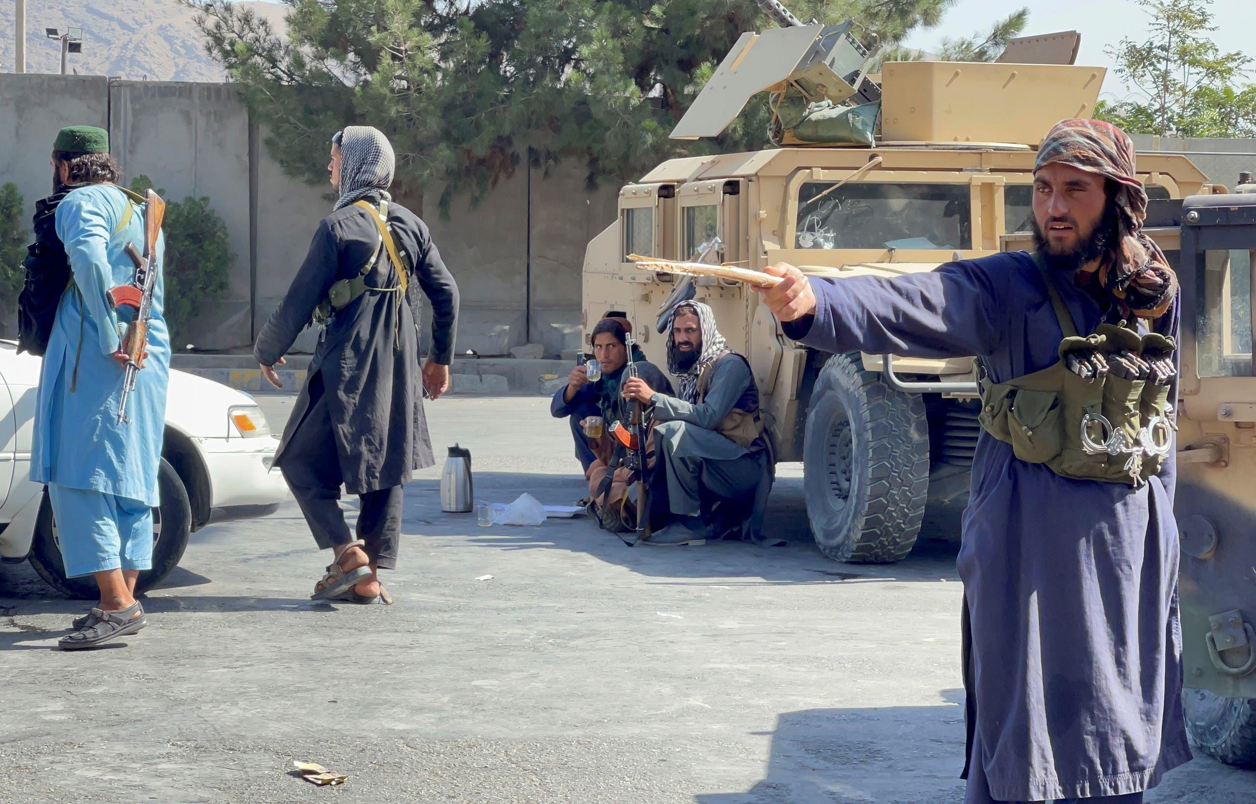 عنصر من طالبان يوجه عصاه نحو محتجين(رويترز)