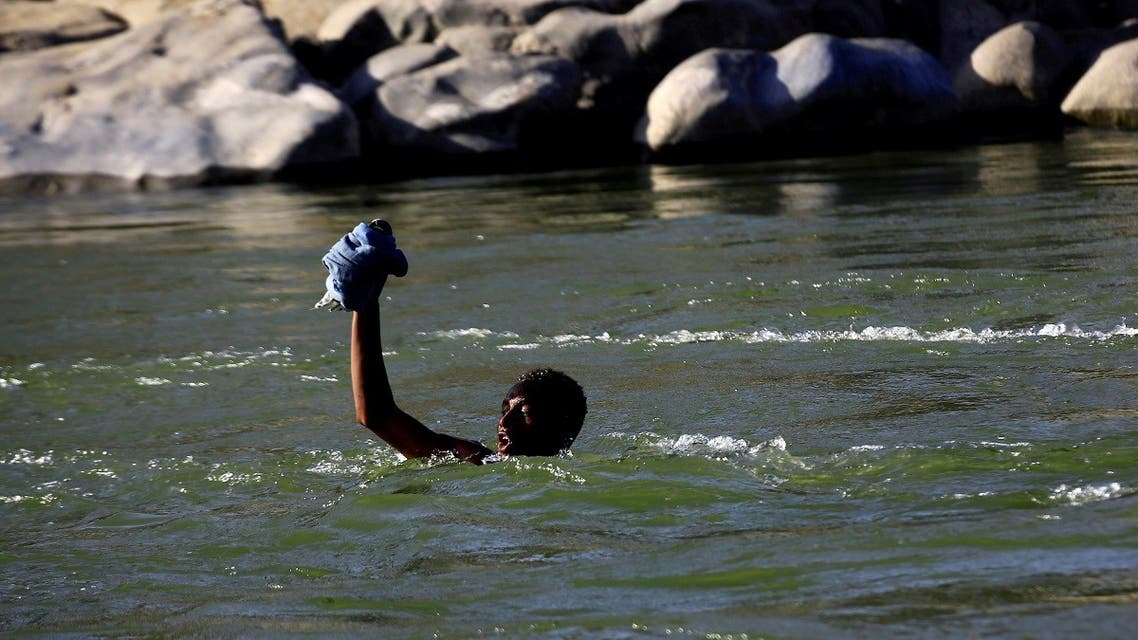 An Ethiopian fleeing fighting in Tigray region lifts his clothes as he crosses the Setit river on the Sudan-Ethiopia border in Hamdayet village in eastern Kassala state, Sudan. (File photo: Reuters)