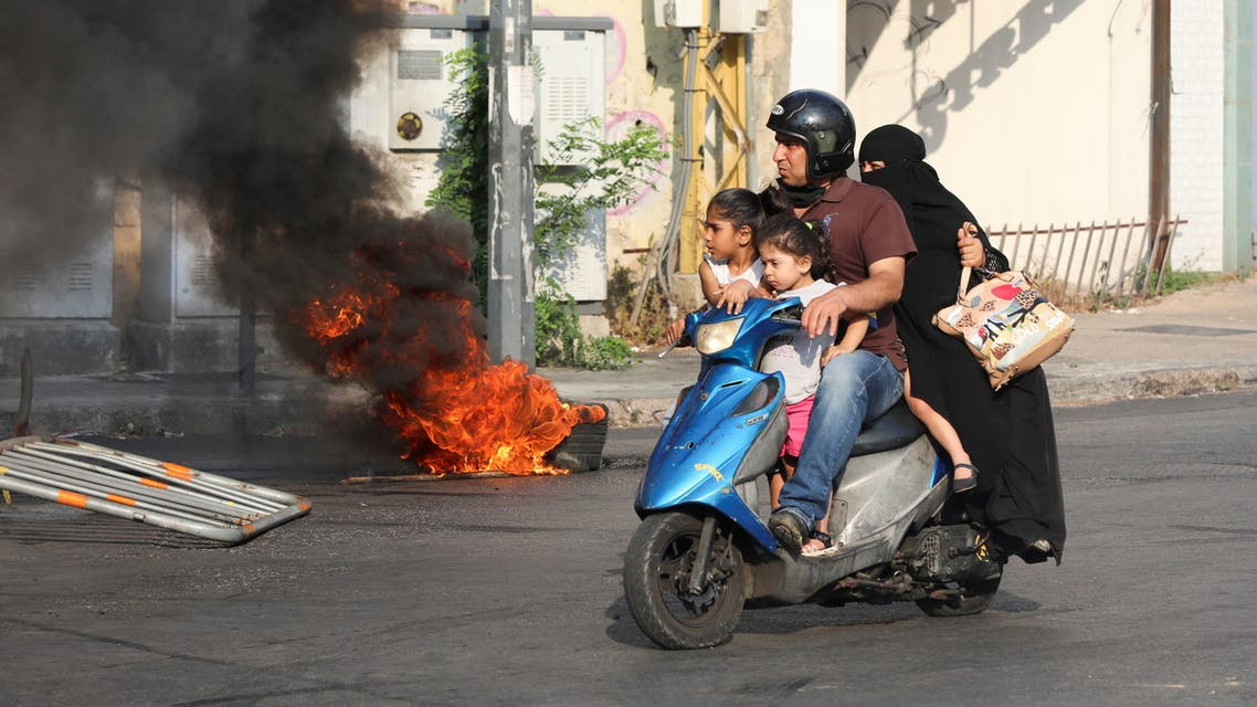A man rides on a motorbike past a burning tyre, during a demonstration by relatives of some of the victims of last year's Beirut port blast, near the Justice Palace in Beirut, Lebanon July 14, 2021. (File photo: Reuters)