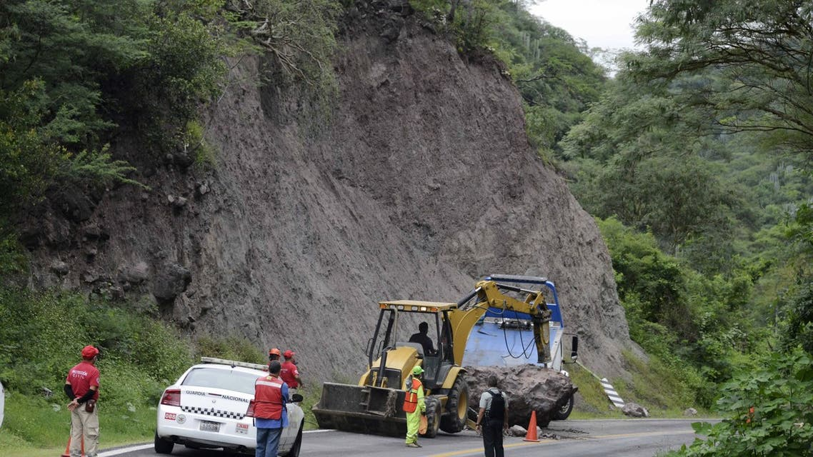 Workers remove rocks on the Acapulco-Iguala highway after a quake in Acapulco, Guerrero state, Mexico on September 8, 2021. (AFP)