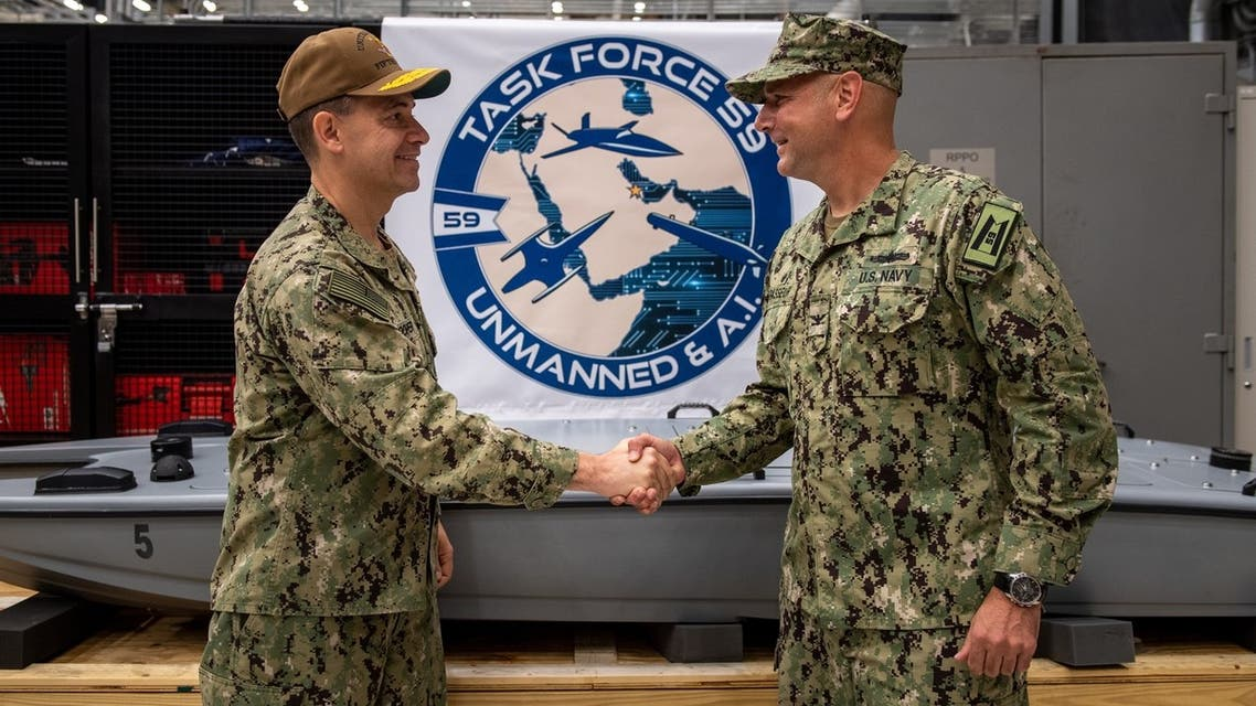 Vice Adm. Brad Cooper, left, commander of U.S. Naval Forces Central Command, U.S. 5th Fleet and Combined Maritime Forces, shakes hands with Capt. Michael D. Brasseur, the first commodore of Task Force (TF 59) during a commissioning ceremony for TF 59 onboard Naval Support Activity Bahrain, Sept. 9. (US Navy)