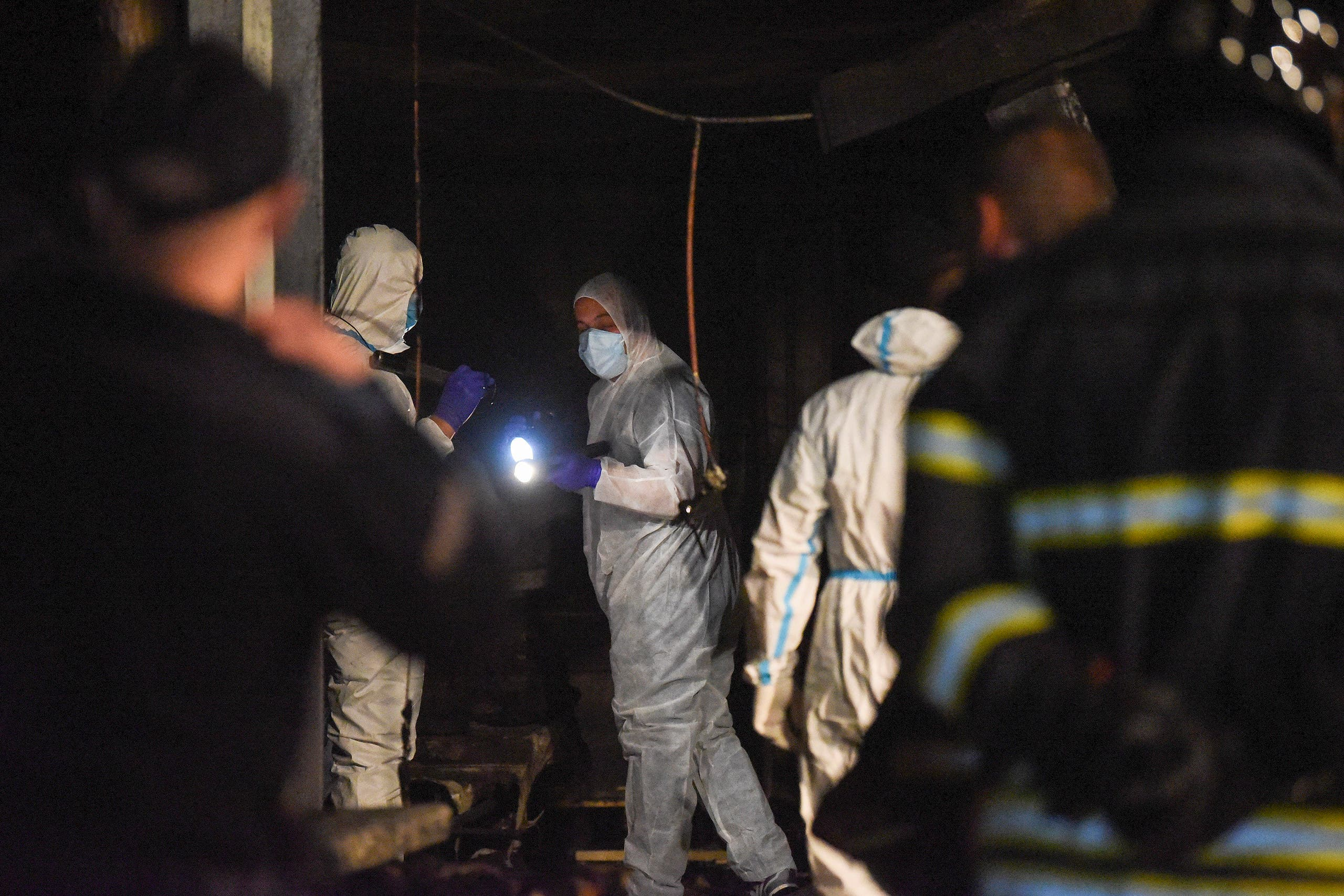Police and firefighters inspect the scene at a COVID-19 clinic after a fire broke out, in Tetovo, North Macedonia on September 8, 2021. (AFP)
