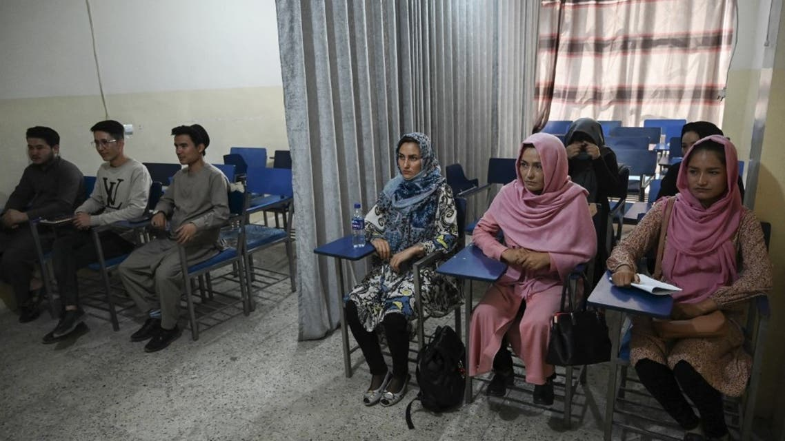 Students attend a class bifurcated by a curtain separating males and females at a private university in Kabul on September 7, 2021, to follow the Taliban's ruling. (AFP)