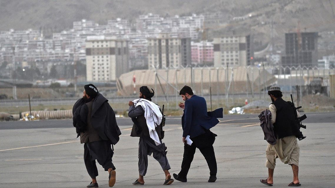 Taliban fighters walk through the tarmac after a Qatar Airways aircraft took off from the airport in Kabul on Sept. 9, 2021. (AFP)