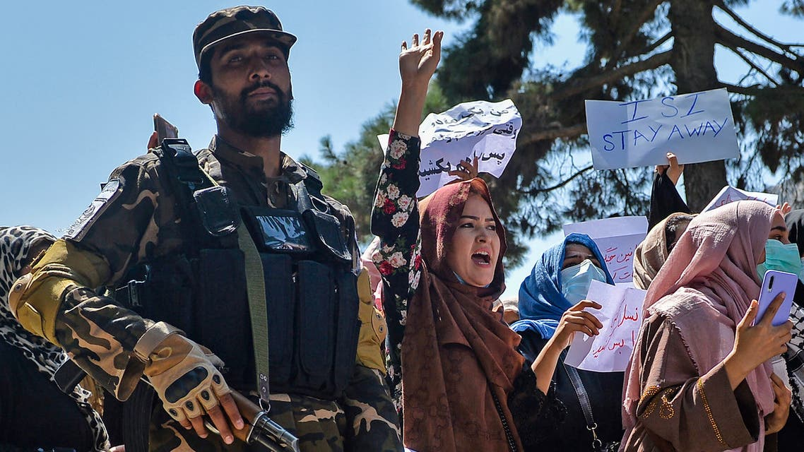 Afghan women shout slogans next to a Taliban fighter during a demonstration in Kabul. (AFP)