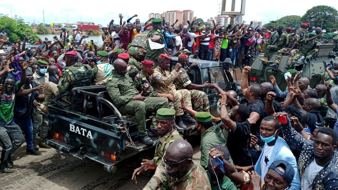 Residents cheer on army soldiers after the uprising that led to the toppling of president Alpha Conde in Kaloum neighbourhood of Conakry, Guinea September 6, 2021. (Reuters)