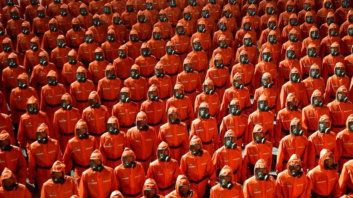 Personnel in orange hazmat suits march during a paramilitary parade held to mark the 73rd founding anniversary of the republic at Kim Il Sung square in Pyongyang in this undated image supplied by North Korea's Korean Central News Agency on September 9, 2021. (Reuters)