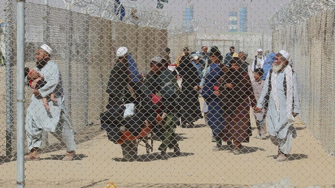Afghan people walk inside a fenced corridor as they enter Pakistan at the Pakistan-Afghanistan border crossing point in Chaman on August 25, 2021 following the Taliban's stunning military takeover of Afghanistan. (AFP)