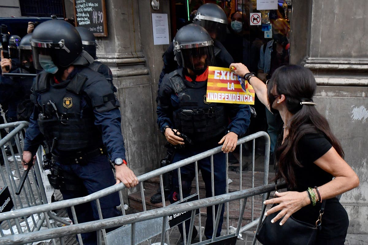 A demonstrator shows a pamphlet fo a member of the Catalan regional police forces following a demonstration marking the Diada, national day of Catalonia, in Barcelona on September 11, 2021. (AFP)