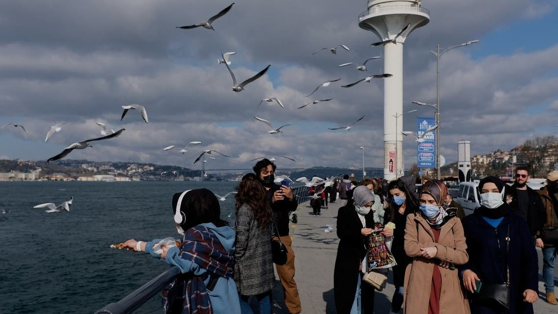 People wearing protective masks stroll by the Bosphorus, amid the coronavirus disease (COVID-19) outbreak in Istanbul, Turkey. (Reuters)