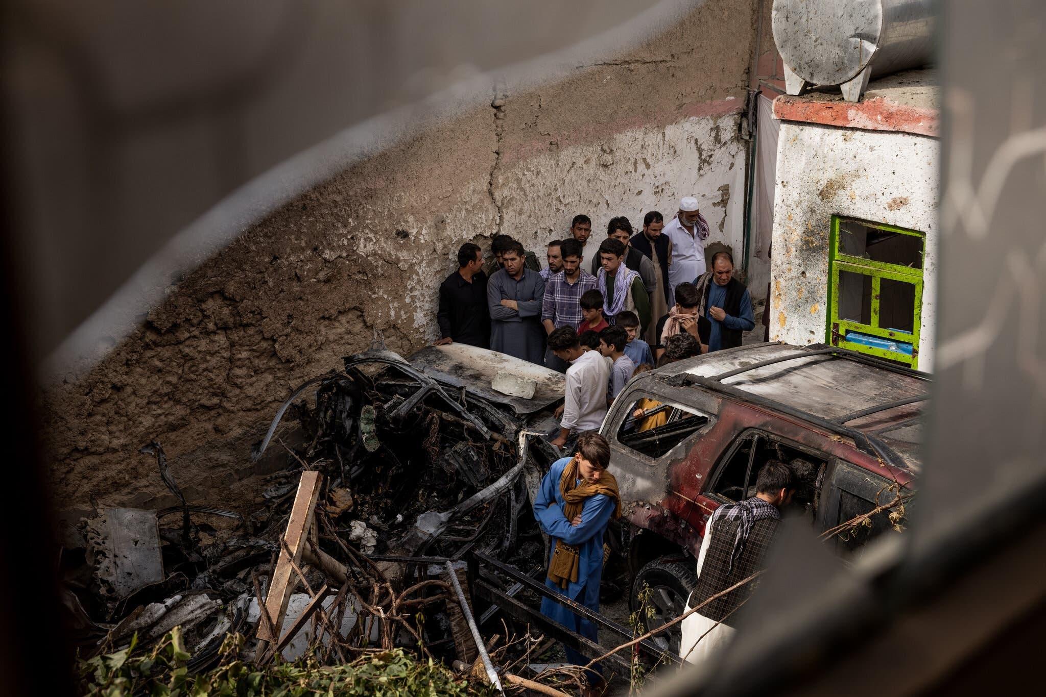 مجموعة من الأفغان يتفقدون السيارة المدمرة عقب الضربة الأميركية