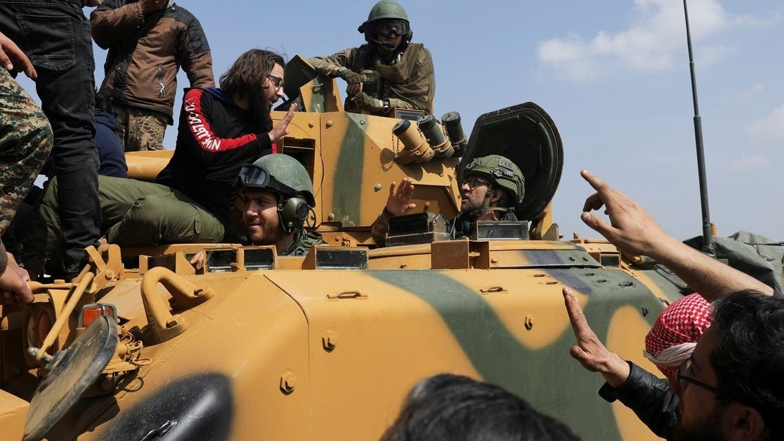 A Turkish soldier gestures as people stand on a military vehicle during a protest against the agreement on joint Russian and Turkish patrols, at M4 highway in Idlib province, Syria. (File photo: Reuters)