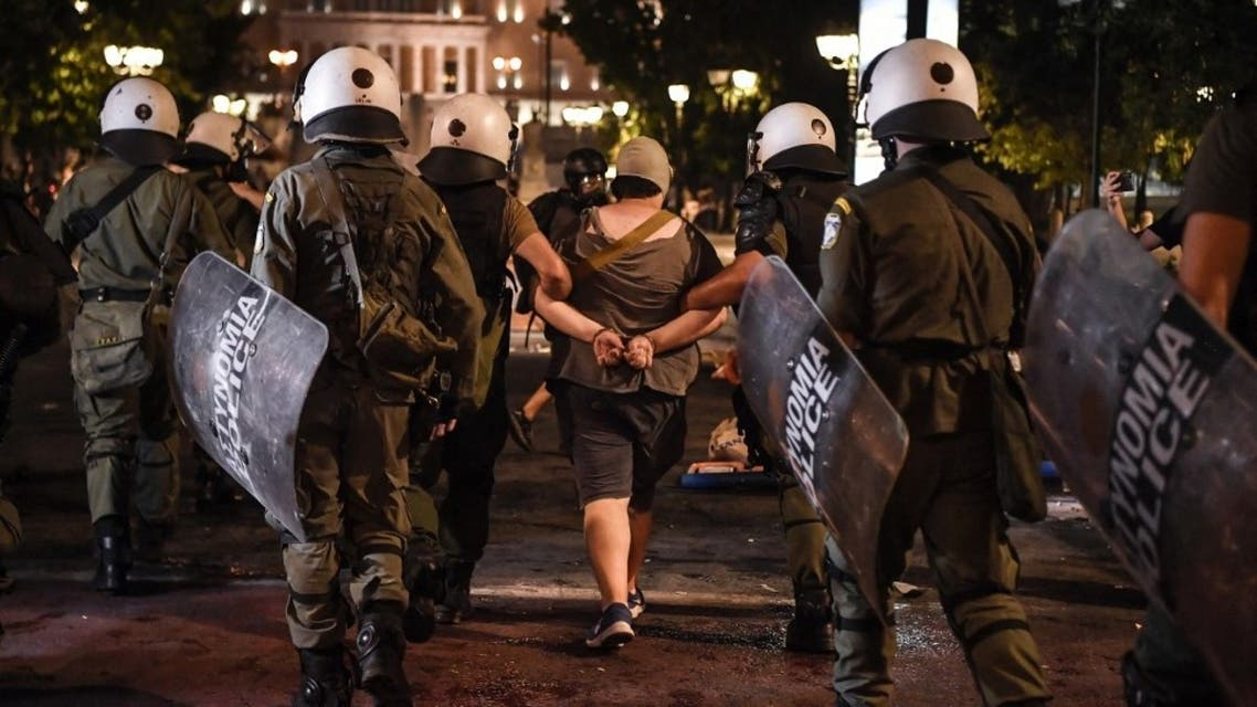 Police detain a protester in Syntagma Square as people protest against the government's plan for mandatory Covid-19 vaccination for health workers, in Athens on August 29, 2021. (AFP)