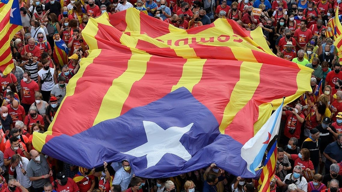 People carry a big Catalan pro-independence Estelada flag during a demonstration marking the Diada, national day of Catalonia, in Barcelona on September 11, 2021. (AFP)